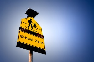 A road sign shown it's a school zone on gradient background.