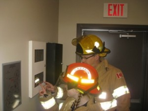 Captain Syd investigating a fire alarm panel.