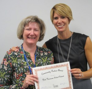 Sandra-Lynn Shortall, District Principal of Early Learning (right) accepts a community partnership award from Occupational Therapist Moray McLean.